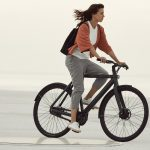 Girl rides electric bike in sthe sunset