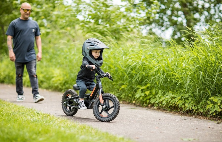 Little boy riding electric motorcycle while father waching